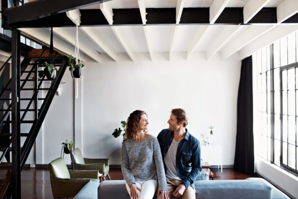 Homeowner couple sitting on sofa in home